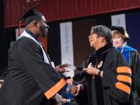 Student shaking hands with faculty at graduation